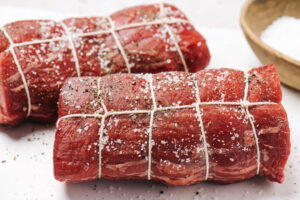 Two beef tenderloin roasts tied with twine and seasoned with salt and pepper on a cutting board.