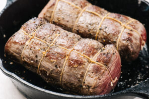 Two beef tenderloin roasts tied with twine and seared in a cast iron skillet.