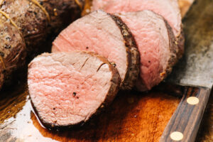Slices of beef tenderloin on a cutting board.