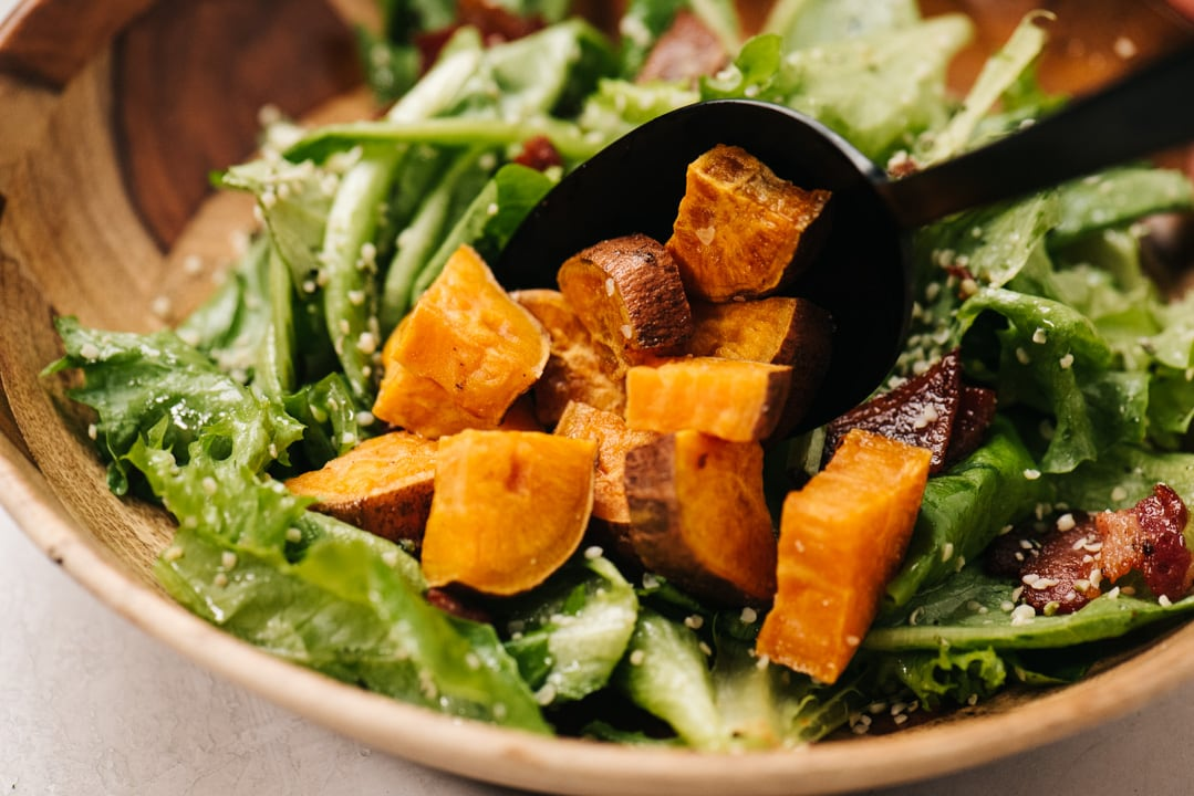 A black serving spoon portioning roasted sweet potatoes onto a bed of salad greens.