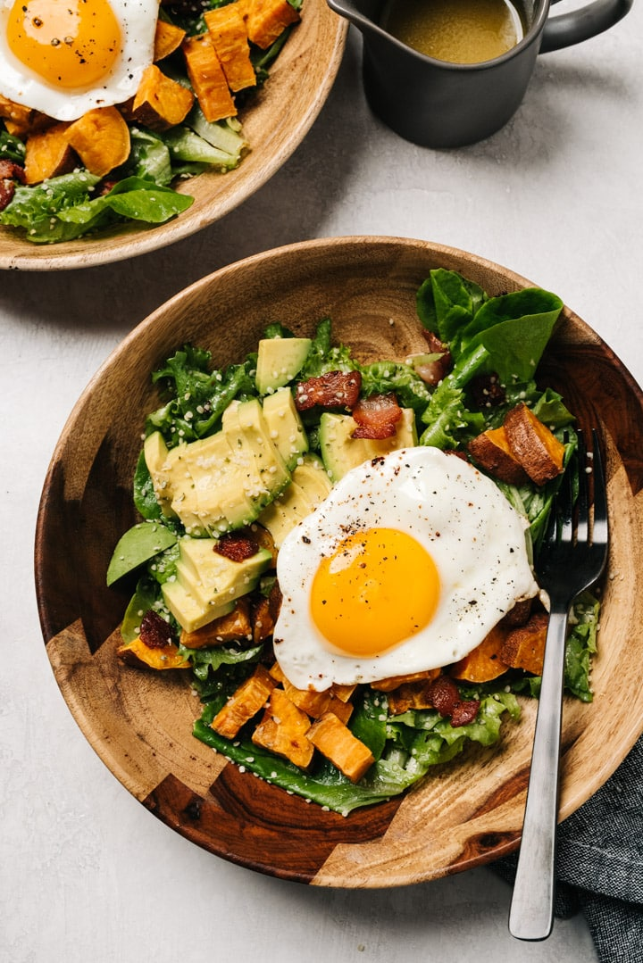 Two breakfast salads in wood bowls with fried eggs on a concreate background with a small pitcher of vinaigrette on the side.