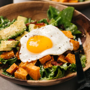 Side view, breakfast salad in a wood bowl with bacon, avocado, sweet potato, and a fried egg in a wood bowl.