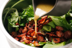 Pouring vinaigrette from a small pitcher into a mixing bowl filled with salad greens and chopped cooked bacon.