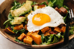 Side view, a fried egg atop a breakfast salad with roasted sweet potatoes and bacon.