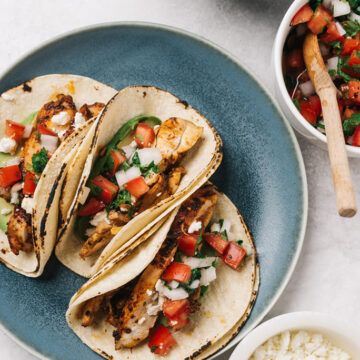 Three chicken street tacos on a blue plate with small bowls of taco toppings surrounding the plate.