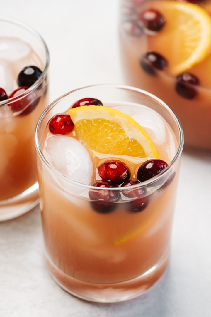 Two glasses of whiskey punch with cranberry and orange on a concrete background with a pitcher in the background.