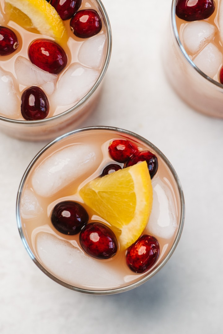 From above, three glasses of whiskey punch garnished with cranberries and orange slices.