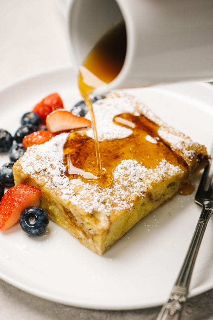 Drizzling maple syrup over a slice of french toast casserole dusted with powdered sugar and served with fresh berries.