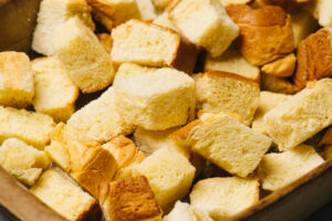 Toasted and dried brioche cubes in a 9x13 casserole dish.