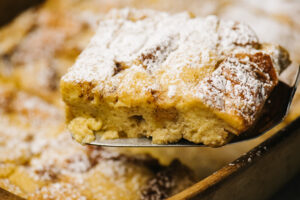 A slice of french toast casserole on a spatula hovering over a casserole dish.