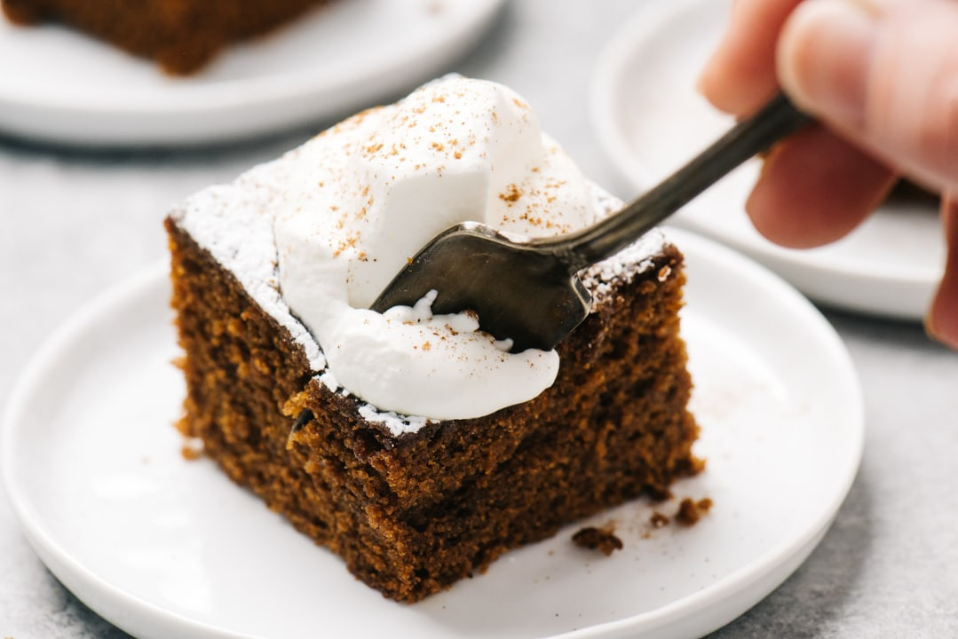 A woman's hand slicing into a piece of gingerbread cake with a fork.
