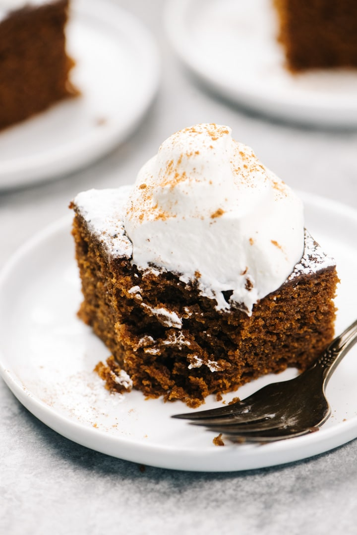 A slice of gingerbread cake with a bit removed showing the moist and tender interior of the cake.