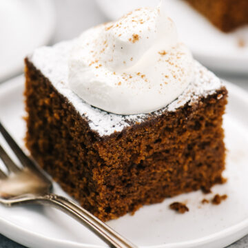 A slice of gingerbread cake topped with whipped cream and powdered sugar with a silver vintage fork.