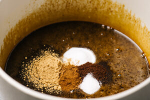Spices and leavening agents added to a bowl of gingerbread cake mixture.