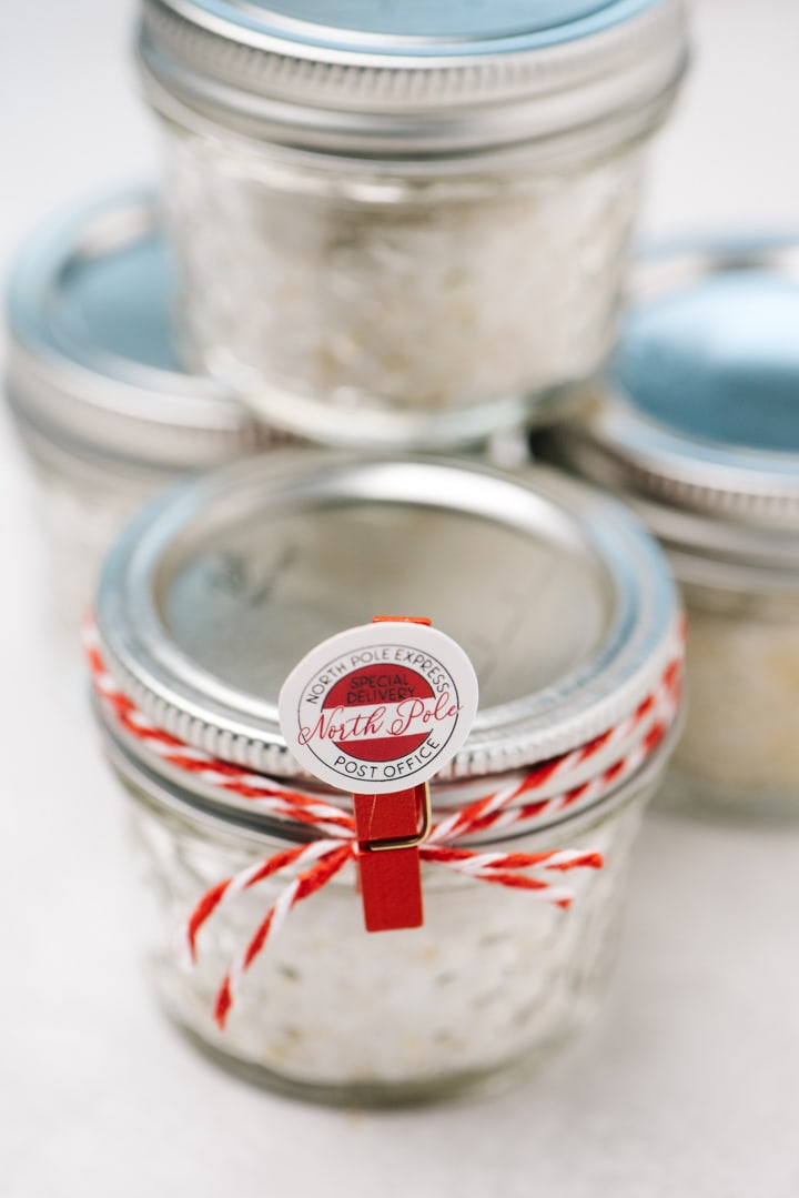 A stack of infused salts packaged in mini mason jars with ribbons.