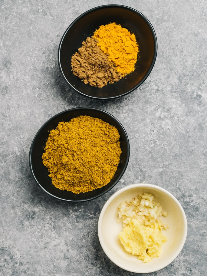 Curry seasonings in small pinch bowls - curry powder, cumin, and turmeric, and finely grated garlic and ginger root.