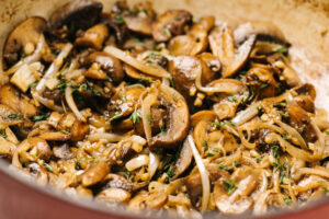 Sautéed onions and mushrooms with fresh thyme in a dutch oven.