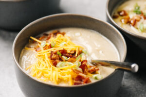 Side view, a bowl of keto cauliflower soup garnished with shredded cheese, bacon, and green onions.