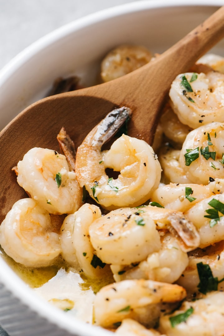 Shrimp scampi in a white serving bowl with a wood serving spoon.