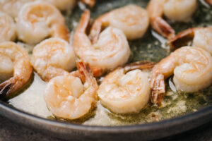 Shrimp sauteed in a butter in a single layer in a skillet.