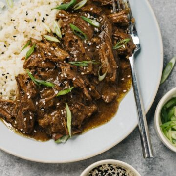 Shredded slow cooker korean beef over cauliflower rice on a blue plate with small bowls of green onions and sesame seeds on the side.