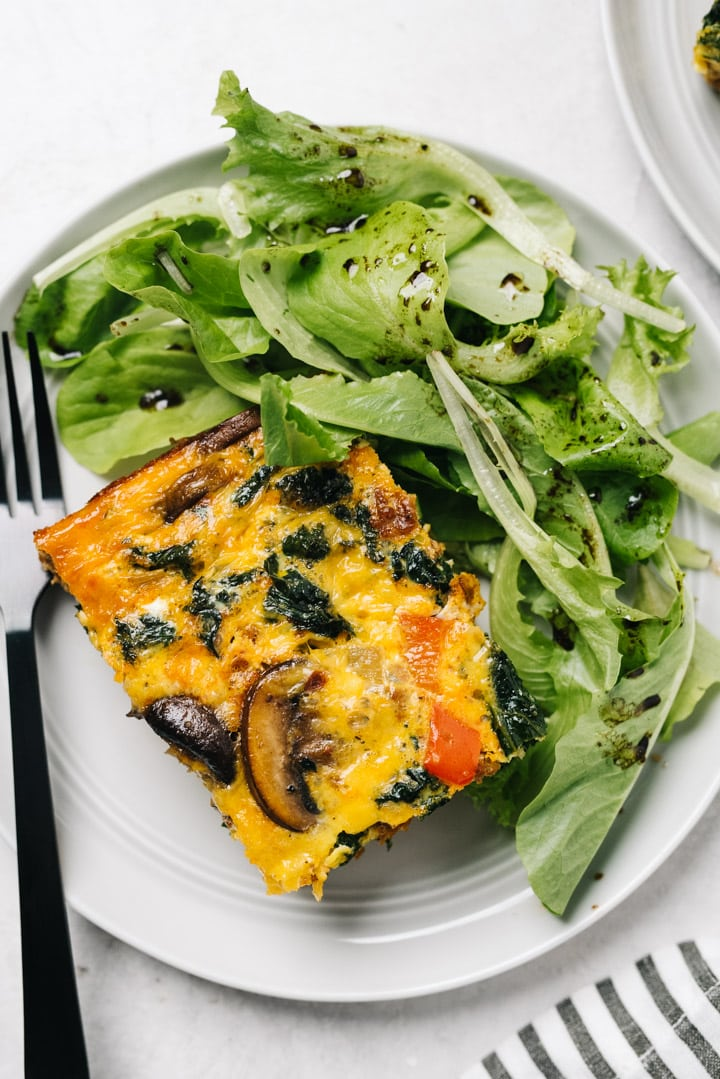 A slice of spicy keto breakfast casserole on a white plate with mixed greens and black fork.