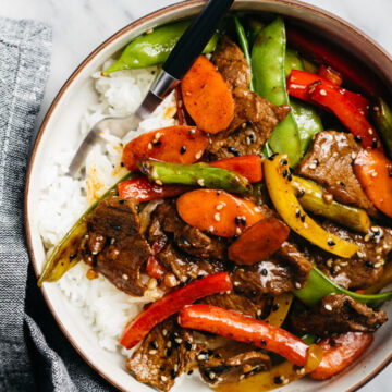 Steak stir fry over white rice in a tan and black bowl on a marble table with a dark grey linen napkin.