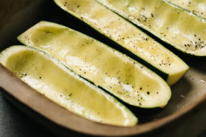 Hollowed out zucchini in a casserole dish, rubbed with olive oil and sprinkled with salt and pepper.