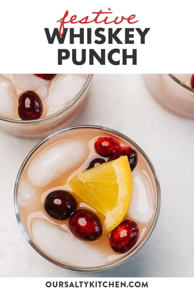 Pinterest image for a holiday themed whiskey punch recipe with cranberry and orange juice.