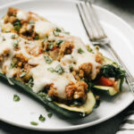 Two italian sausage zucchini boats on a white plate with a silver fork.