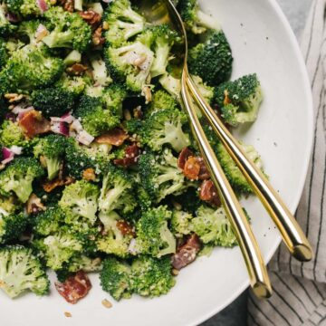 Keto broccoli salad with bacon and creamy poppy dressing in a white serving bowl on a concrete table with a striped linen napkin.