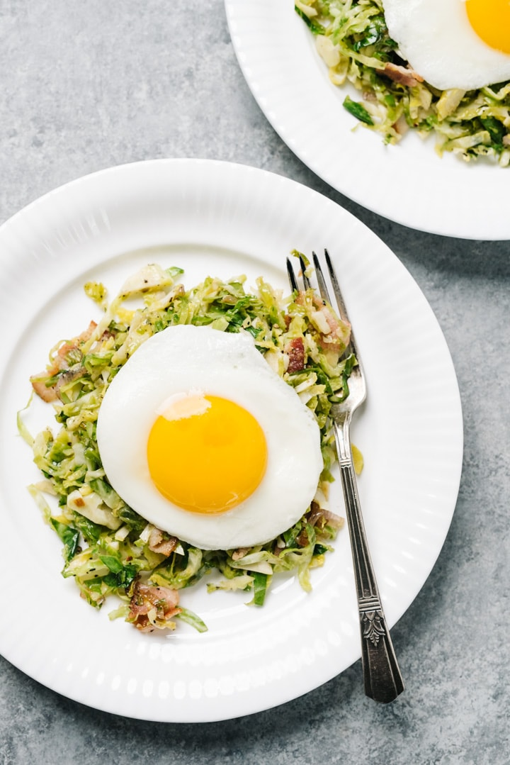 Two white plates with brussels sprouts hash topped with a fried egg.