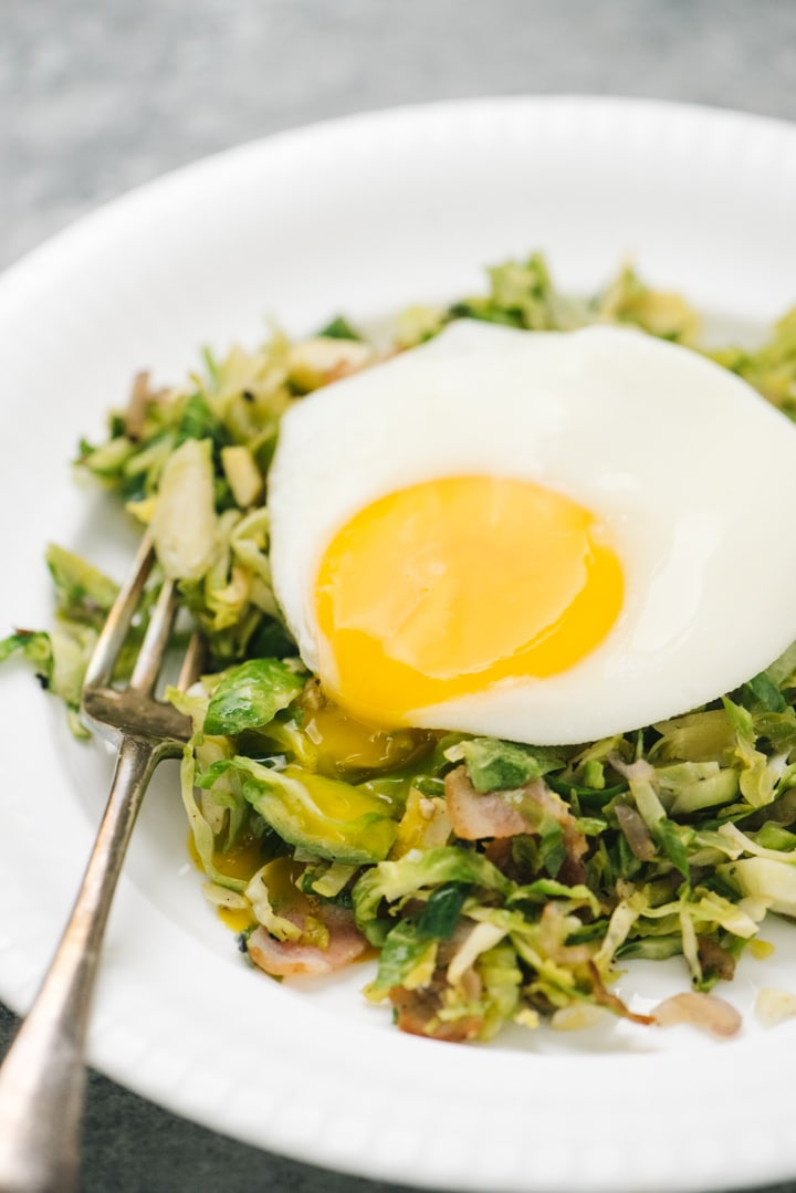 Side view, a fried egg with a broken yolk running over a pile of brussels sprouts hash on a white plate with a silver fork.