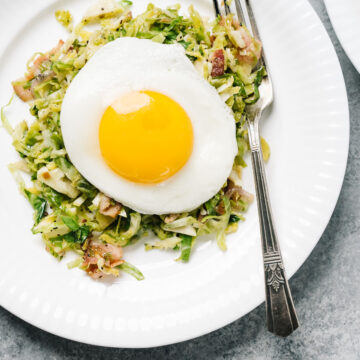 Brussels sprouts hash on a white plate topped with a fried egg, with a silver vintage fork.