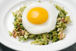 Side view, brussels sprouts hash on a white plate topped with a fried egg.