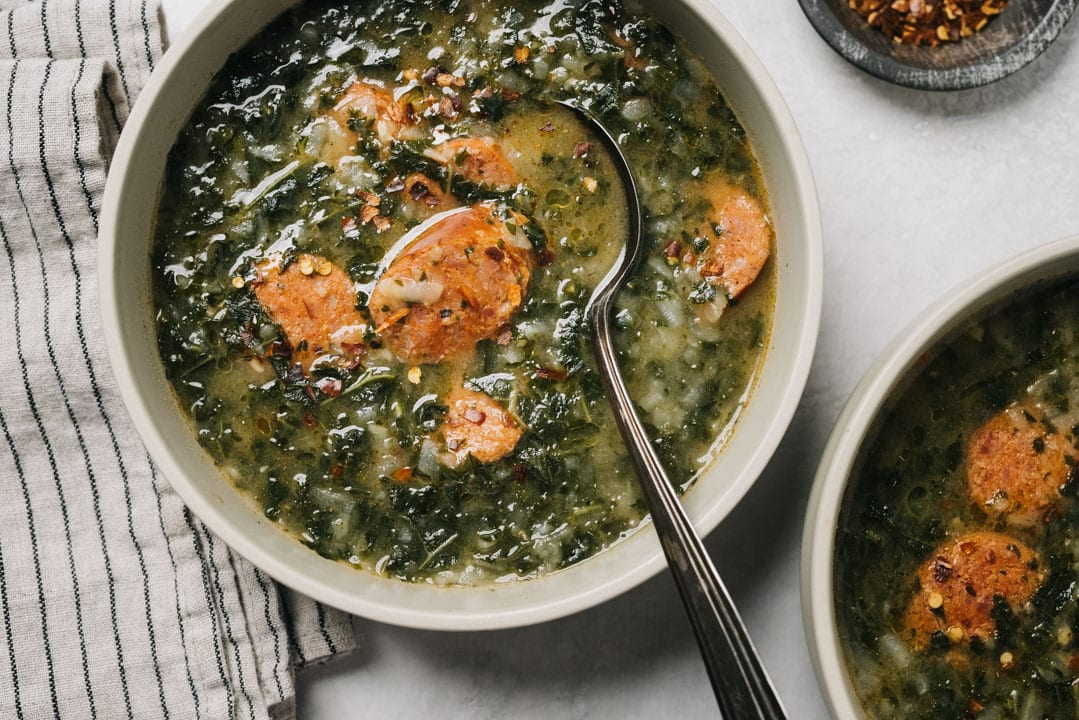 Two bowls of Portuguese green soup with sausages on a concrete background with a striped linen napkin and small dish of red pepper flakes.