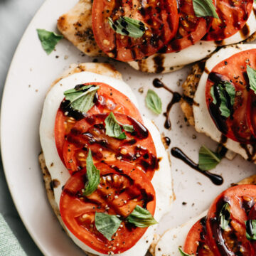 Four caprese chicken breasts on a tan platter with mozzarella, fresh tomatoes, basil, and balsamic drizzle.