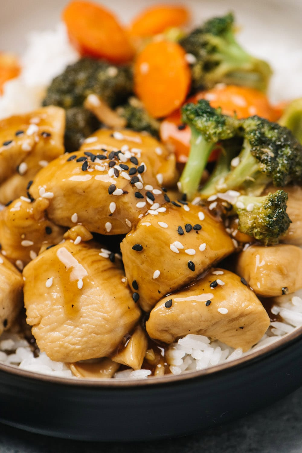 Side view, chicken teriyaki in a bowl with rice, carrots, and broccoli.