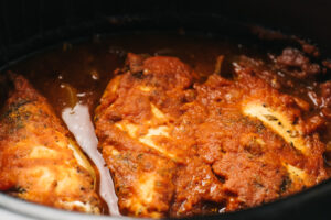 Cooked chicken tinga in a slow cooker before being shredded.
