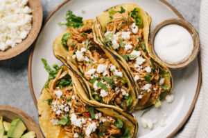 Three chicken tinga tacos in corn tortillas with cilantro and queso fresco on a white plate.