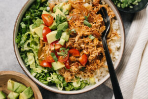 Slow cooker chicken tinga over cauliflower rice and shredded lettuce, topped with tomato and avocado, in a bowl on a concrete background.