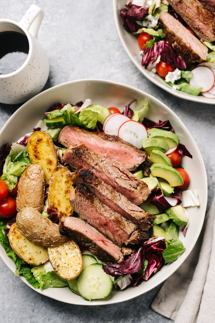 Steak salad with roasted potatoes and avocado in a tan salad bowl on a cement background with a small pitcher of balsamic dressing.