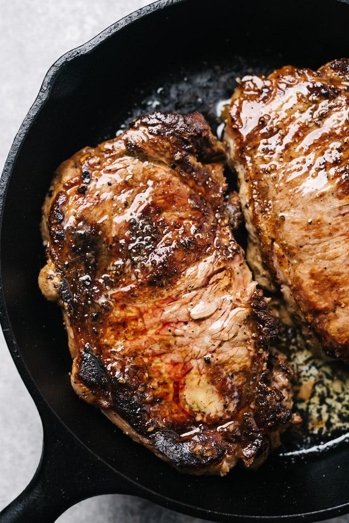 Seared sirloin steaks in a cast iron skillet.
