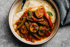 Sausage and peppers over cauliflower puree in a bowl with a dark grey linen napkin.