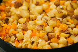 Diced yukon gold potatoes with bell pepper and onion, sautéing in a cast iron skillet.