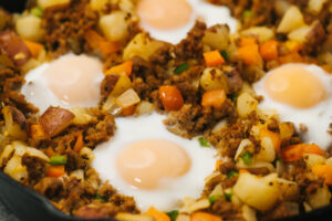 Cooked potato hash with chorizo sausage and eggs in a cast iron skillet.