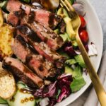 Whole30 or keto steak salad in a tan salad bowl with a gold fork - seared sirloin, avocado, salad greens, blue cheese or roasted potatoes, and balsamic dressing.