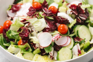Steak salad salad base tossed in a bowl - romaine lettuce, radicchio, tomatoes, cucumbers, and radishes.