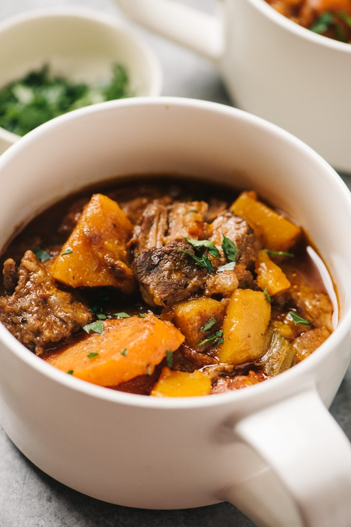Side view, slow cooker beef and butternut squash stew in a cream colored crock with a small bowl of parsley in the background.
