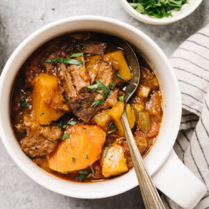 A bowl of slow cooker whole30 beef stew with butternut squash on a concrete table with a striped linen napkin and small bowl of chopped parsley.
